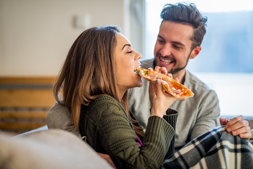 Young couple eating pizza in bed